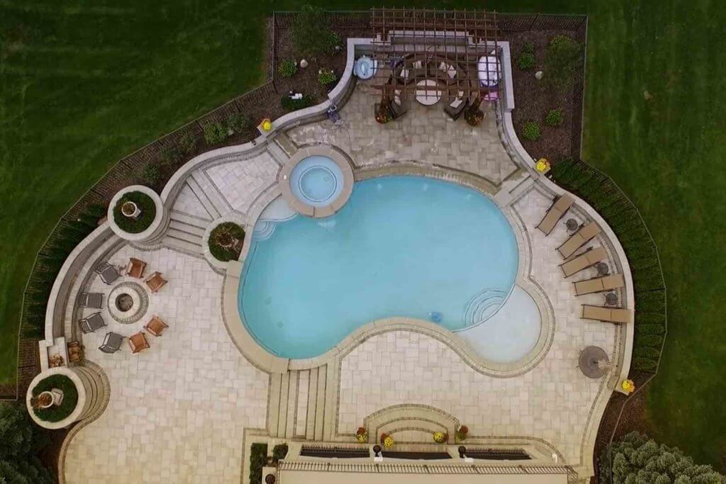aerial view of pool with spillover spa, fire pit, patio and outdoor seating