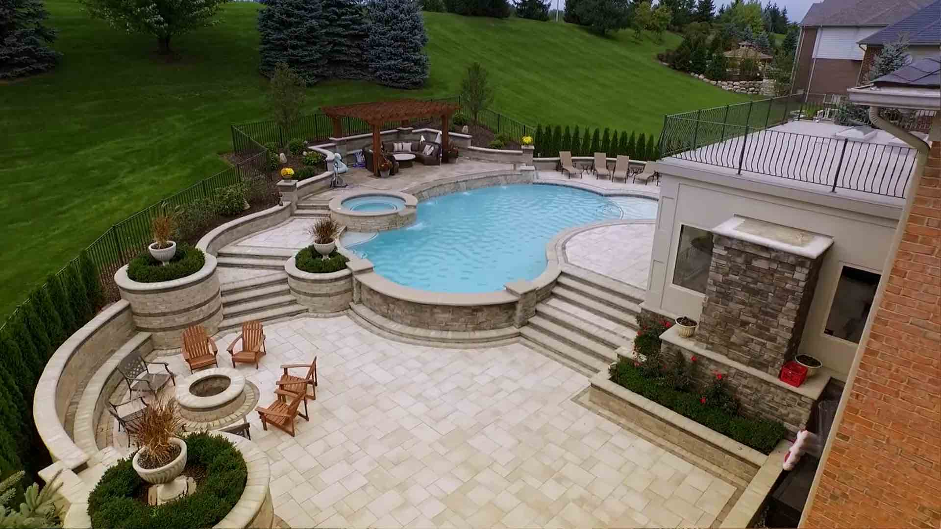 view of backyard patio, fire pit, seating, pool and spillover spa
