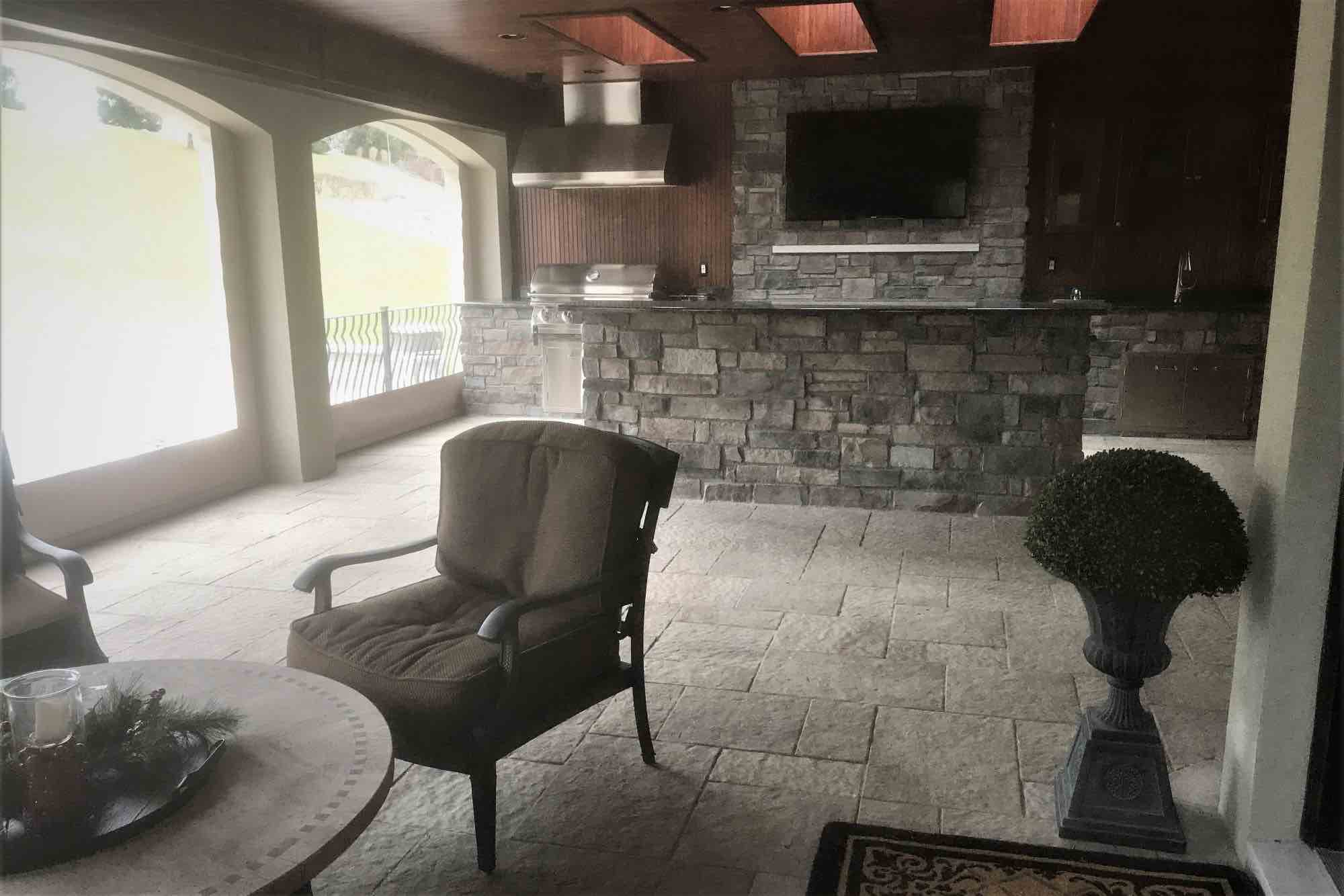 kitchen with bar facing patio seating and outdoor fireplace