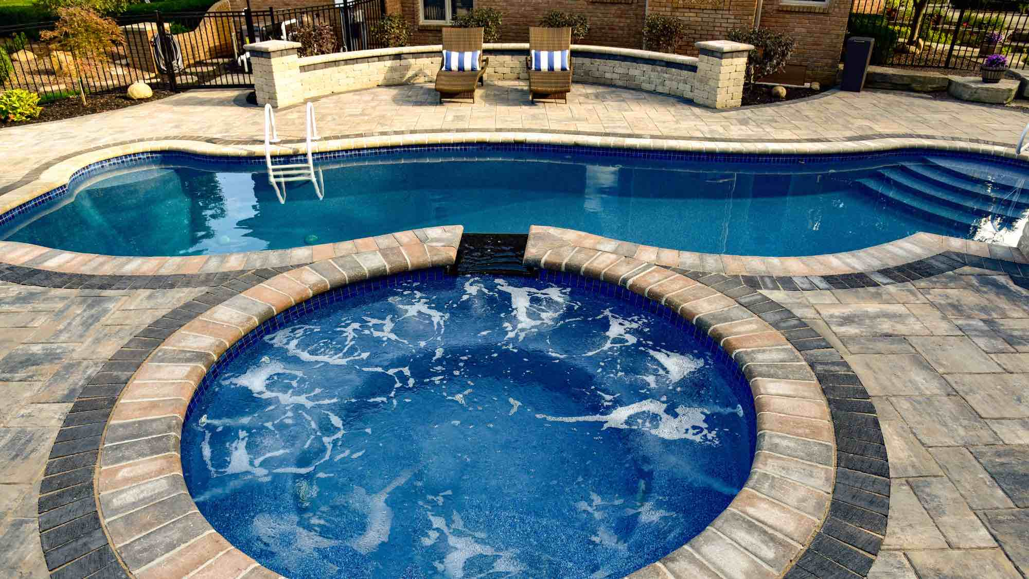 Hot tub with spillover into pool