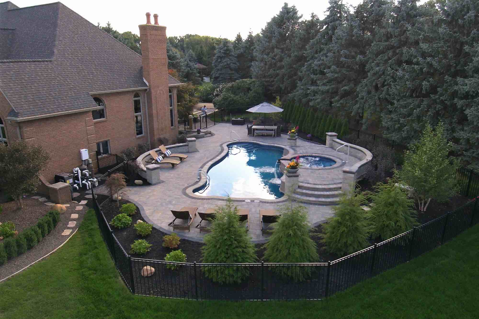 aerial view of backyard pool with hot tub spillover attached