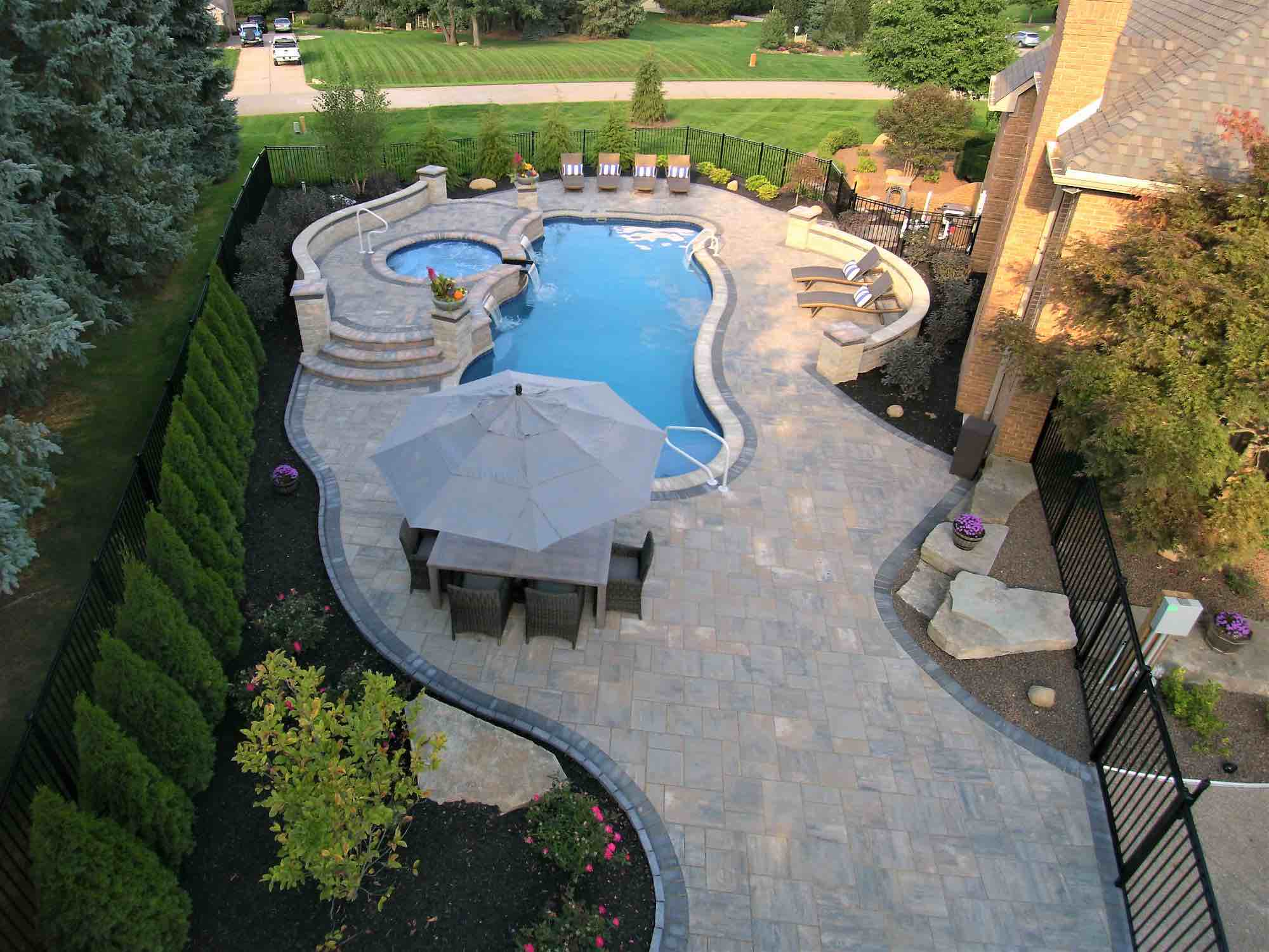 aerial view of pool with a spillover hot tub