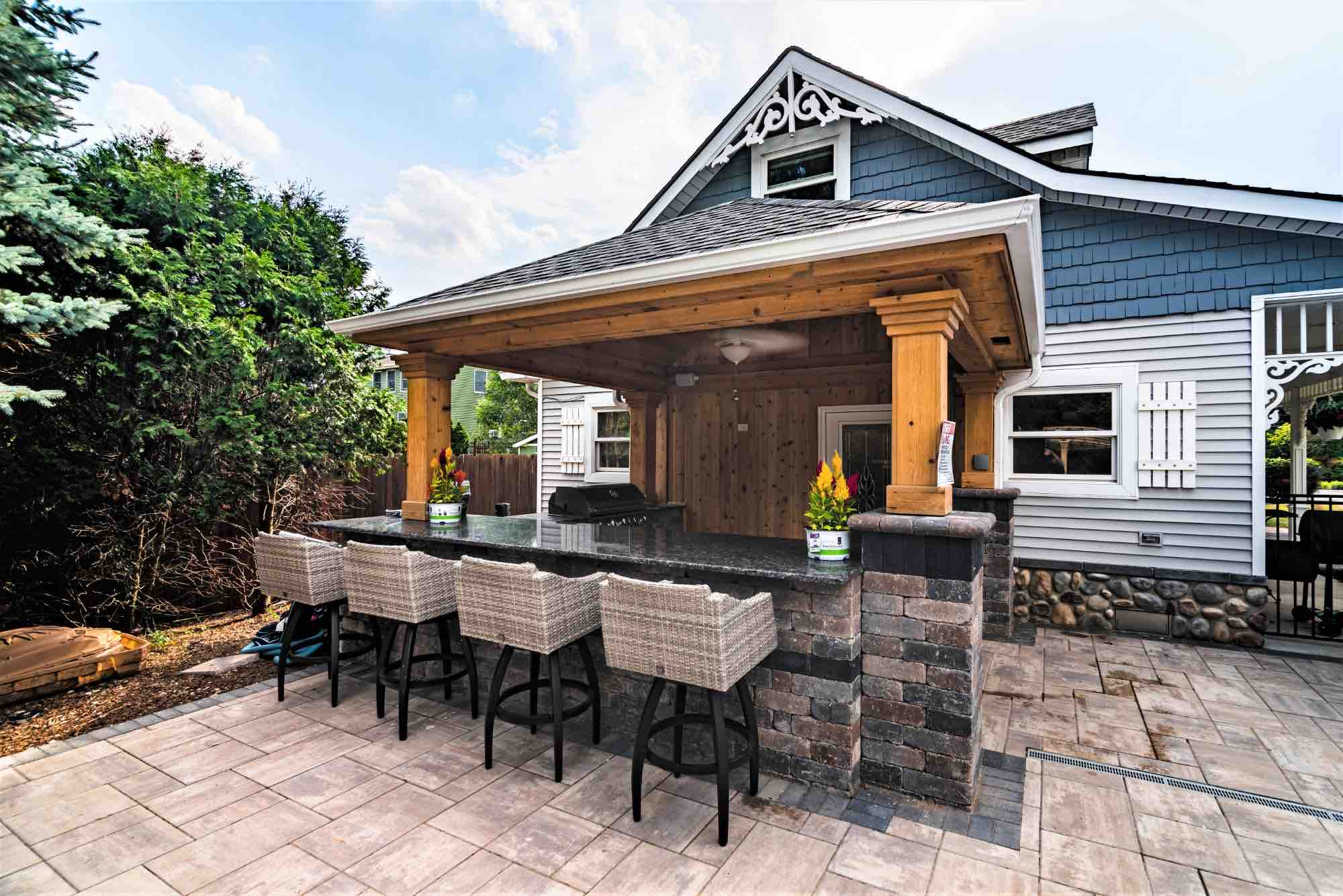 outdoor kitchen and bar seating next to pool