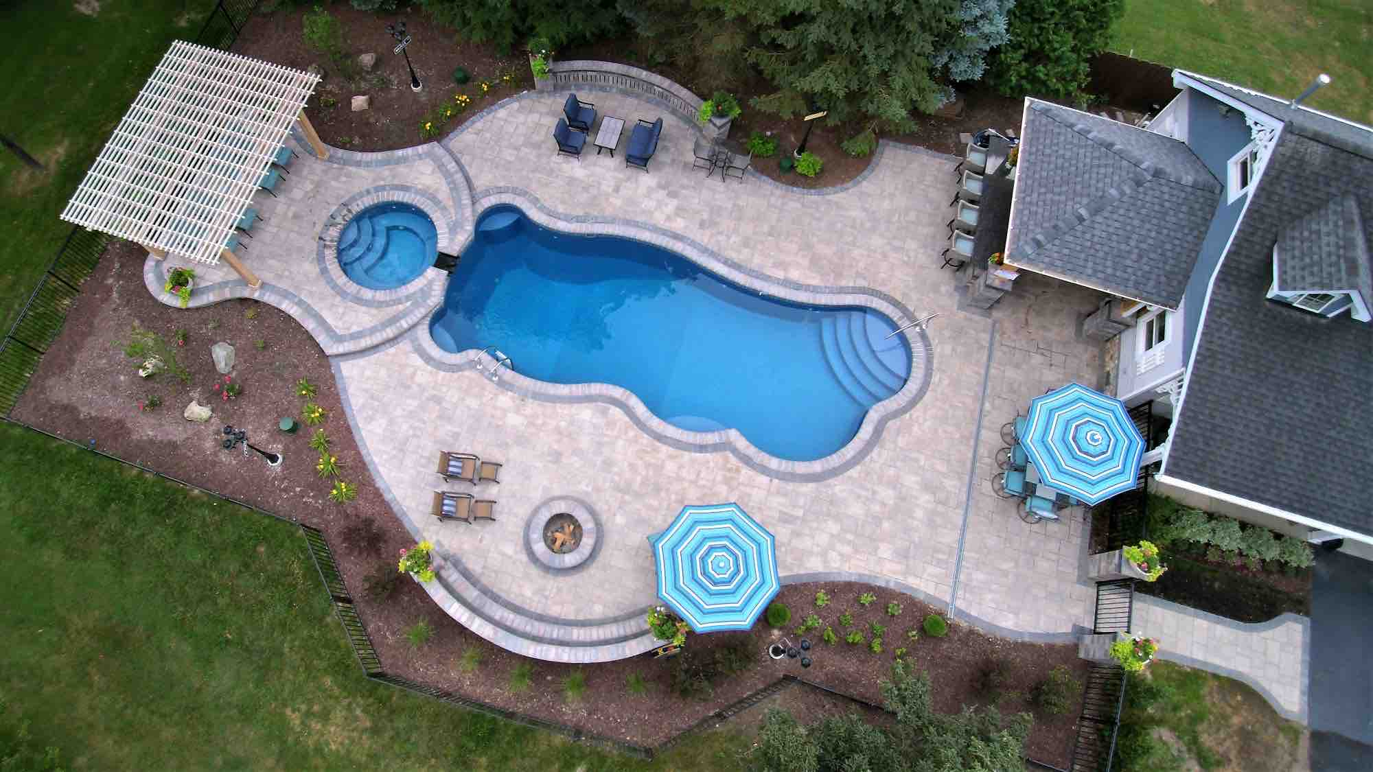 aerial view of pool and hot tub with poolside lounge, deck seating, fire pit, and outdoor kitchen