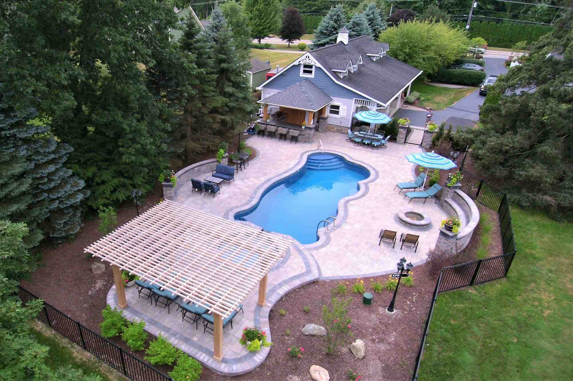 aerial view of pool and poolside lounge with outdoor kitchen and fire pit